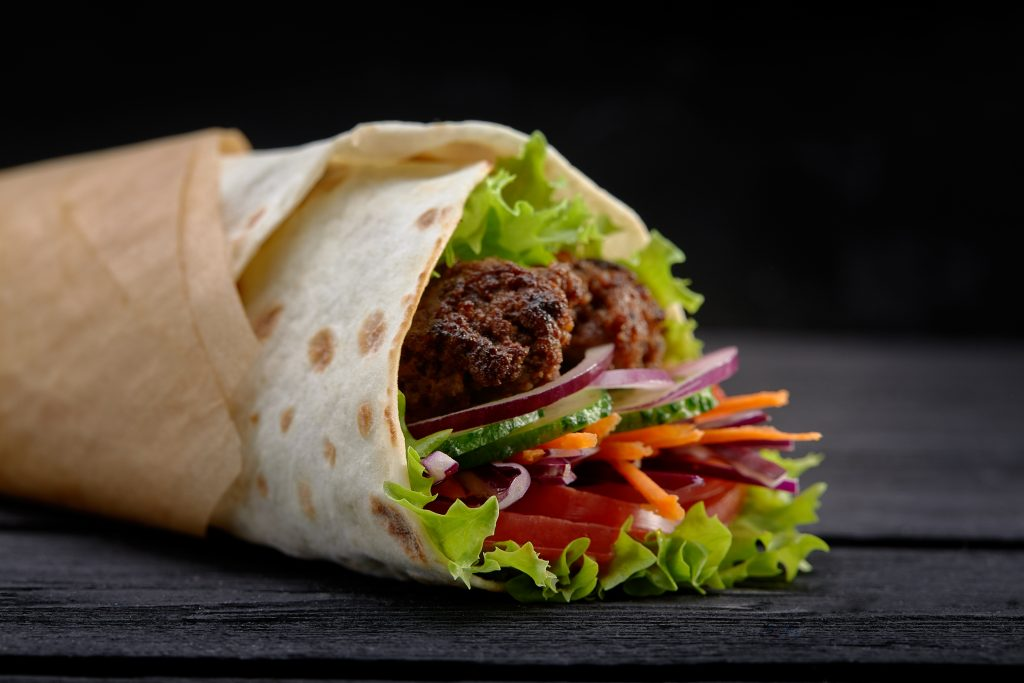 Tasty doner kebabs with fresh salad trimmings and shaved roasted meat served in tortilla wraps on brown paper as a takeaway snack.