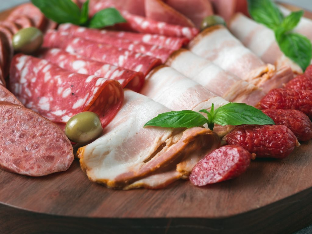 Antipasto set platter on wooden plate close up. Cold smoked meat plate with sausage,sliced ham,prosciutto, bacon, olives and basil. Appetizer on wooden tray cut tree sawed imitation. Copy space
