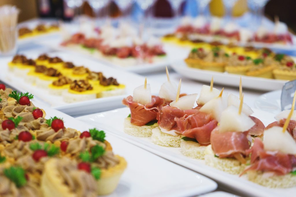 The classic Spanish tapas ham and melon. Food delivery service and catering meals on the table during the event. Soft focus.