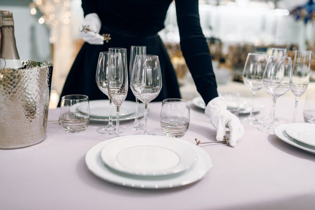 Waitress in gloves puts the knife, table setting. Serving service, festive dinner decoration